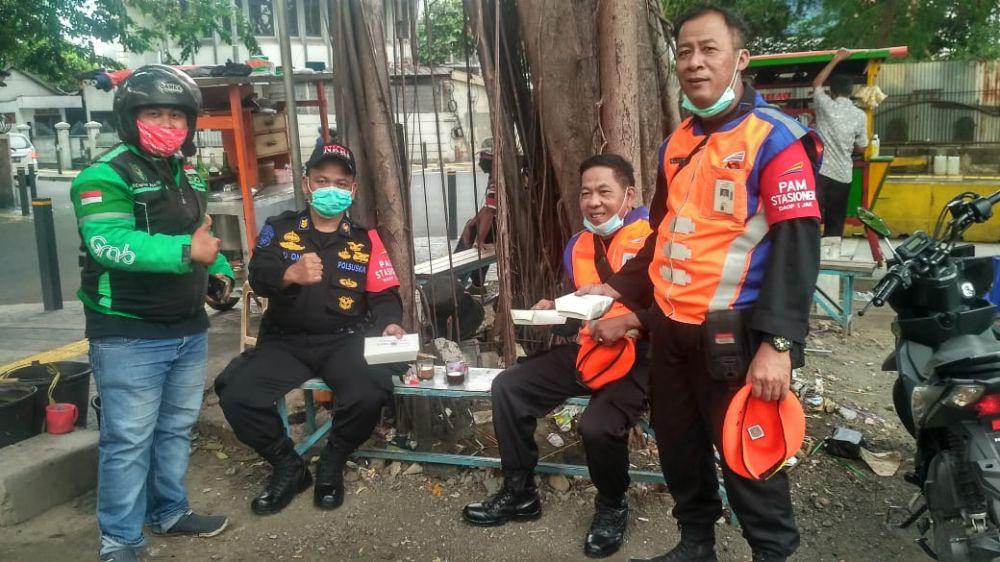 STB dan Gerakbareng.com membagikan nasi kotak kepada keamanan setempat. (Foto: Surya/Advokasi.co)