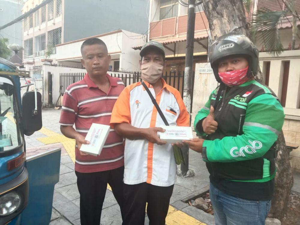 Pembagian nasi kota kotak kepada masyarakat. (Foto: Surya/Advokasi.co)